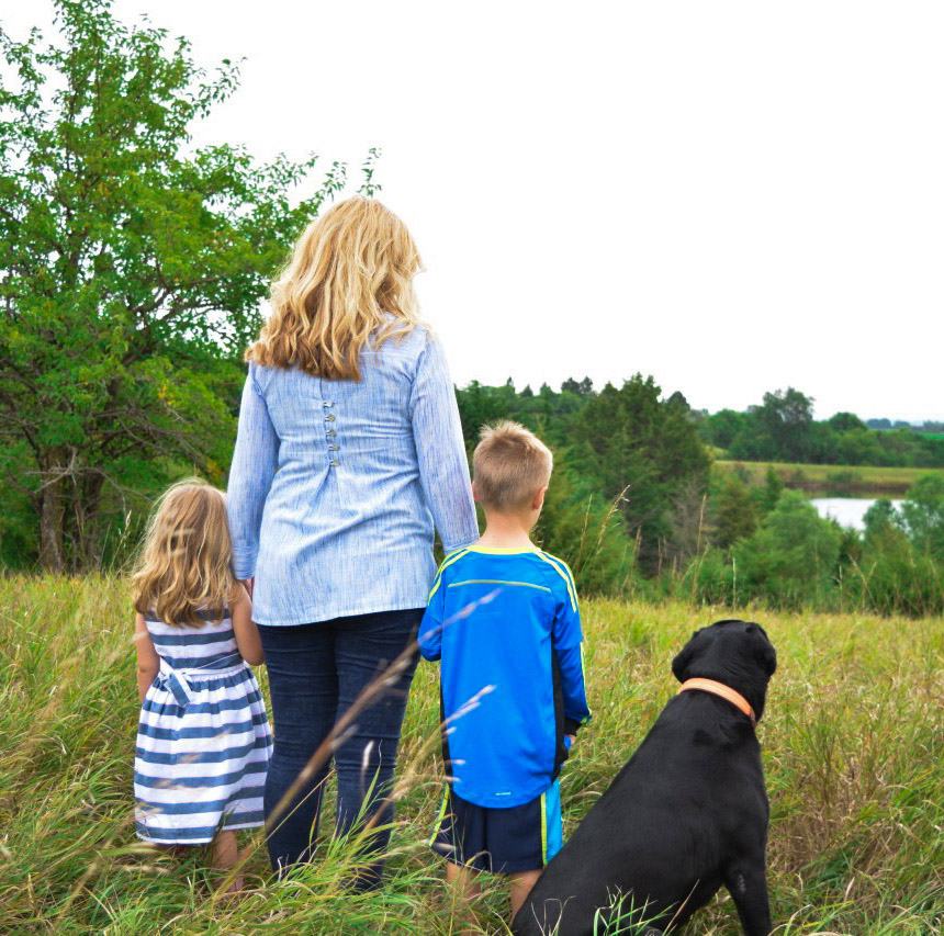 kari warberg standing in front of lake with her kids and dogs